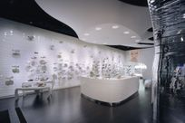 Interior of a white shoe store space. A white counter as well as white tables displaying shoes are placed in the venter of the room. A long white wall with a wave pattern utilizing the Puck system has various shoes propped up against the wall for display.