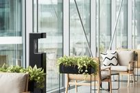 A black hand sanitizer stands amongst wooden and cushioned chairs and plants in a room with large glass windows.