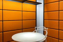 White tall chairs are paired with a white round table within a room with orange paneled walls. Black System 1224 shelves are placed along the left wall of the space.