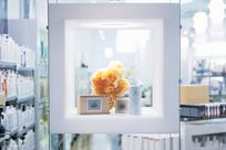 A white thick cubic frame holding various beauty products for display is held up in the air by four thin cables and rods. The cube is photographed in front of a mainly white beauty store.