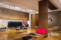 Interior of a store. Various wooden displays are placed around the room showcasing different products such as shoes and bags. Wooden Fortina panels are lined along the walls as well as propped up on the floor to divide off a little section for chairs.