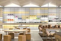 A large space furnished with brown furniture and wooden tables. The wall is made up of gray and yellow panels using wooden and white System 1224 shelves to display a variety of different colored lamps.
