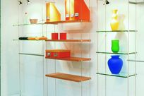 Several wooden and glass shelves are held up by thin cables and rods with the shelves displaying various colorful items including vases and boxes.