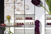 Interior of a beauty store. Lit LED panels with a photography of flowers and petals are placed on the wall with white shelves holding up various beauty products.