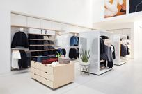 Interior of a white store. Wooden and white display cabinets display a variety of clothes. Against the back wall, wooden and white System 1224 shelves are used to display more clothes.