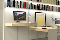 System 1224 shelves along a white paneled wall carry multiple objects such as books but also a monitor and keyboard, as well as lamps and a picture frame.