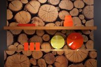 Infused Veneer panels of a large stack of logs in varying sizes hosts two wooden shelves, each displaying various orange and yellow ceramics and fabric.