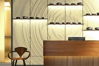 Wooden counter sits in front of a LED paneled wall displaying a yellow and gray pattern. Gray lit System 1224 patterns are laid against the wall holding stones of various sizes.