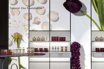 """A large paneled wall with an image of flowers, petals, and """"Natural. Our Foundation."""" printed on it are utilizing white System 1224 shelves displaying different beauty products."""