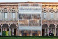 Metal Fortina panels are placed vertically in a rectangular shape in front of a large elegant building.