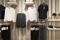 Various clothes are on display on hangers and shelves along a wall made up of white vertical Fortina panels.