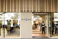 View of the entrance of the Kit and Ace store. Large glass windows reveal the inside of the store. The Kit and Ace logo is printed in a thing tan wall. Above the glass and wall are wooden Fortina panels placed vertically.