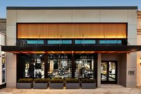 Exterior of FRYE's store. Metal panels make a rectangular shape around the exterior of the store. Within the metallic panels are wooden lit Fortina panels placed vertically with glass windows underneath.