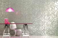 A pink glass table, pink overhead lamp, and silver chair are placed int front of a large silver and abstract patterned Iconic Panel wall.