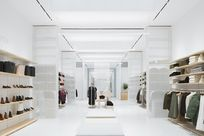 White and wooden benches are centered in a white space. Along the left and right walls, wooden System 1224 shelves are lined displaying a variety of shoes, clothes, and bags.