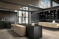 Interior of a modern home kitchen. Black shelves are propped up against black walls and panels utilizing the Puck system. On display on the shelves are various white and black vases and bowls. A black and wooden counter is placed in the center of the room with black tall chairs.