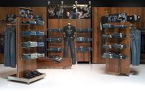Interior of a denim store. Wooden panels utilizing the Puck system are both placed against the wall as well as propped up around the store holding shelves carrying denim pants for display.