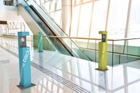 """3 hand sanitizers—blue, green, and yellow—are placed around a hallway with the words """"Welcome back!"""" printed on them in white. Behind the hallway is a large escalator and glass windows."""
