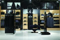 Interior of a high-end store. Wooden panels utilizing the Puck system are propped against a black floral patterned wall. Glass shelves on the panels display various dark and gray colored business attire. Black displays and panels also using the Puck system to hold shelves are also placed throughout the room.