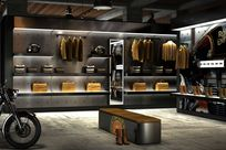 Interior of a store. Multiple motorcycles and a long seating bench are placed around the room. A silver wall utilizing the Puck system holds several lit black shelves displaying various bags, fabrics, helmets, and jackets. On the right is a lit paneled wall with a cropped image of a motorcycle printed on it also using the Puck system to display boots and jackets.