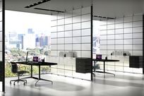 Multiple sections are separated using white Sorbetti panels. White System 1224 cabinets are placed along the wall furnished with white books. Within the space, black chairs and tables are paired with working laptops.