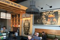"""View of a coffee shop. A wooden panel with the words """"Welcome to the Box"""" printed hang over the building, closing in the counter space where various foods are displayed on sale. Within the wooden structure, an Infused Veneer Panel of a sculpture of Buddha's face is printed largely."""