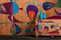 Colorful patterned wooden Infused Veneer wall stands behind a cabinet with the same patterning as the wall.