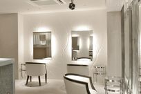 Multiple white chairs are seated facing multiple back lit mirrors. The mirrors are placed in front of branch patterned white Iconic Panel walls.