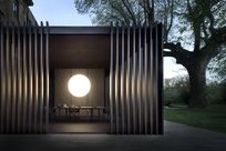 A cubic space stands surrounded by nature. A large white orb shaped lamp lights up the inside of the space revealing a table with chairs. Fortina panels are propped vertically along the front of the room.
