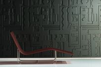 A sleek wooden lounge chair is placed in front of a dark olive colored wall with Iconic Panel displaying geometric shapes.