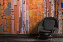 A gray loveseat sits in front of a large colorful rectangular and circular patterned decorated Infused Veneer panel wall.