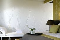 A bedroom with green, white, and gray sheets against a green wall are placed alongside a white lounge chair against a white wall with branch patterned Iconic Panel.