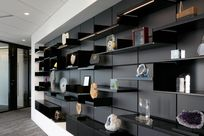 Black System 1224 shelves are placed along a black wall showcasing a variety of miscellaneous decorative objects such as stones and trophies.