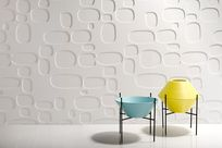 Blue and yellow ceramic ware are propped up on black steel poles in front of a large white wall decorated with circular patterned Iconic Panels.