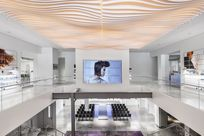 View of a large mall space. On the left and right walls, images of women and makeup products are printed on paneled walls with System 1224 shelves displaying beauty products. In the center, a large screen hangs over a staircase leading down of a woman looking to her side.