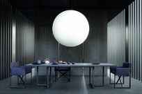 An elegant gray-toned room with a large white orb shaped lamp hanging over a table set with teapots. Gray Fortina panels stand lined up on each side of the room, enclosing the space.