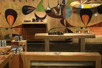Large colorful patterns on Infused Veneer panels decorate the wooden walls as well as wooden displays of a room. Various decorated products are set on display.