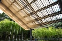 Wooden Fortina panels are laid vertically together to create an outdoor ceiling along with black columns propping up the roof.