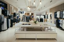Interior of a clothing store. A large wooden table with white chairs are placed in the center of the room. Along the left and right walls, poles are set out displaying various clothes.