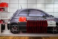 A paneled wall with an image of a car printed on it utilizes System 1224 shelves to display a variety of different red and white merchandise.