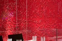 A table holding glass waters and a salad with chairs are placed in front of a large red abstract linear decorated Iconic Panel wall.