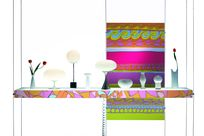 Various lamps, vases, and tulips are placed on top of a colorfully decorated shelf standing against a colorful fun patterned panel held up by thin cables and rods.