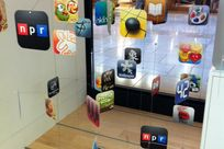 """Multiple different app icons including """"npr"""" and """"Cut the Rope"""" are cut out into round edged squares and strung up on cables and rods above a wooden floor."""