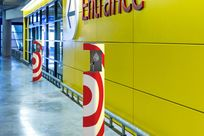 """Two white hand sanitizers with red targets decorated the exterior stand in a line in front of a yellow wall with the sign """"Entrance"""" printed in red on it."""