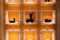 Nine white cubic frames each displaying various cameras and binoculars are hung up by metal cables and rods against a pale orange background.