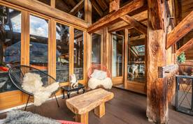 Outdoor terrace with wooden coffee table and modern armchairs at La Ferme de Margot luxury chalet in Morzine