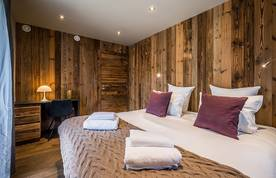 Double bedroom with wooden walls and fresh towels at Moulin I luxury chalet in Les Gets