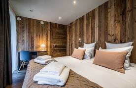 Wooden double bedroom with a desk at Moulin II luxury chalet in Les Gets