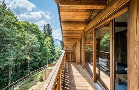 Wooden terrace with forest views at Moulin I luxury chalet in Les Gets