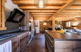 Fully-equipped modern kitchen with orange juice and baguette at Balata luxury chalet in Morzine